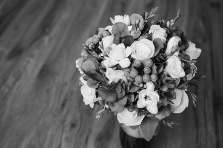 colorless: Wedding bouquet of white and blue flowers in a transparent vase stands on a light background. White Rose. Morning bride