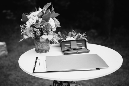 Black and white art photography monochrome, beautiful unusual wedding decor. Rustic Style. Pen in a case, the layout on the table. Flowers in a basket.