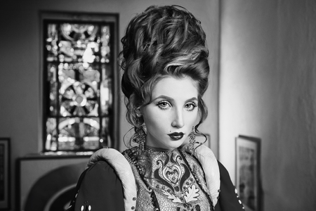 Black and white art photography monochrome, girl with blue eyes in red dress. Queen with a high hairdo. Vintage image. A woman with pale skin Stock Photo