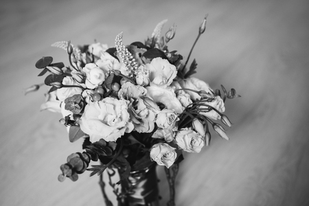 Wedding bouquet of white, red and pink flowers in a vintage vase stands on a light background. White and pink roses. Morning bride, copyspace