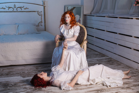 sits on a chair: Two beautiful girls with red hair in a beautiful white wedding Victorian dresses. Female style. The fragile girl. Thin waist. A woman sits on a chair. Conceptual photography. Girl lies on the floor