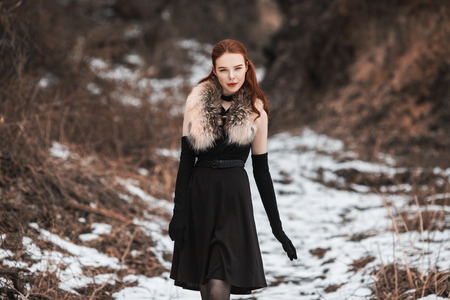 Striking girl with long red hair in black clothes. Woman in black dress and fur around neck, with long black gloves posing on background of winter nature. Female street style. Beautiful elegant model Stock Photo