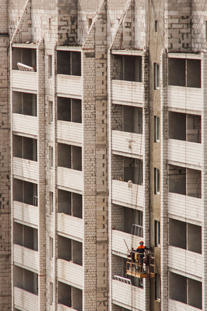steeplejack: Construction worker in uniform in the cradle aligns the wall. Plasterer. Construction works