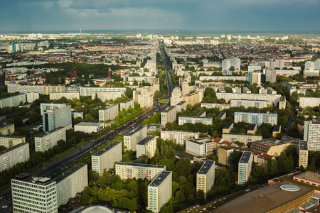 megapolis: Travel to Germany. View of the houses and streets of Berlin with a birds-eye view. Overcast sky. Light from the sun on the houses. Residential houses. Megapolis. European city