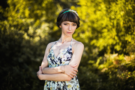Beautiful girl with dark hair and brown eyes with a wreath on her head in a summer dress on a green background. The woman in the forest on a sunny day. Model posing on the nature.