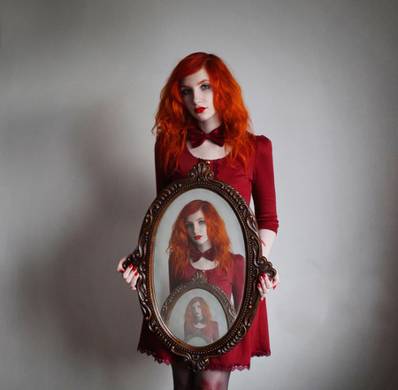 Woman with long red curly hair in red dress with bow tie on neck hold a mirror with reflections on white background. Red-haired girl with pale skin, blue eyes with bright appearance and sweet face.