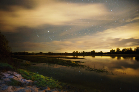 Beautiful night starry landscape. Stars reflected in the water. Astrophotography. Clear starry sky. Slow shutter speed. The spectacular sky. Scenic view.