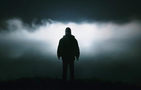 Silhouet van een man in de duisternis. Nachtfotografie. Dichte mist over de rivier. Stockfoto