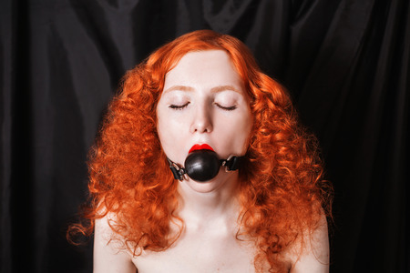 Violence, woman with long red curly hair gagged. Red-haired girl with pale skin, blue eyes, a bright unusual appearance on a black background. The frightened look. BDSM