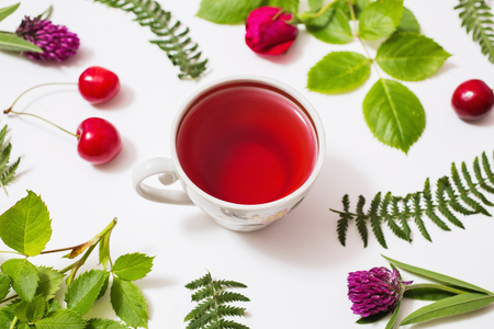 passion fruit flower: Red tea in a cup, green blades of grass with purple flowers, leaves, birch twigs rose with red flowers, green ferns, ripe cherries lie on a white background. Flat lay, top view. Herbal decoction Stock Photo
