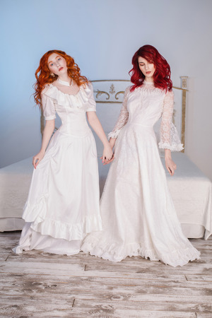 Two beautiful girls with red hair in a beautiful white wedding Victorian dresses. Female style. The fragile girl. Thin waist.