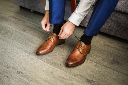 남자는 구두를 신다. 신발에 끈을 묶어 라. 남자 스타일. 직업. 회의 준비를 위해 일을 준비하십시오.