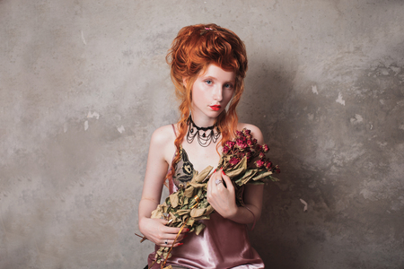 A woman with red hair in a nightgown. Red-haired girl with pale skin and blue eyes with bright unusual appearance with choker around her neck with a bouquet of dried roses. French courtesan. Copyspace Stock Photo