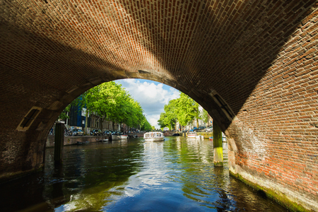 Spring sunny Amsterdam. The bright clear blue sky with white clouds. Boat trip on the canals of Amsterdam. The bridge over the water. Travel to Europe Stock Photo