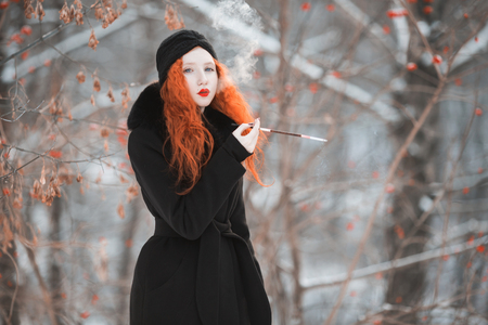 A woman with red hair in a black coat on background of a winter forest with a mouthpiece in hand. Red-haired girl with bright appearance with a turban on her head with a cigarette. Smoking aesthetics Stock Photo