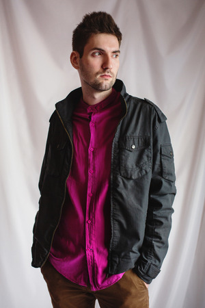 Young attractive cheerful man with dark hair with a beard in a purple shirt and a black jacket on a white background. Mens style. Male portrait. Studio photography