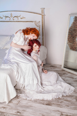 Two beautiful girls with red hair in a beautiful white wedding Victorian dresses. Female style. The fragile girl. Thin waist. Two women sitting in the bedroom on a white bed