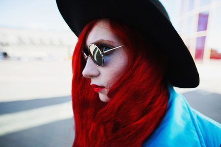 Woman with red curly hair in blue coat and black round glasses on background of big city. Red-haired girl with pale skin and bright appearance with black hat on head. Street style Stock Photo
