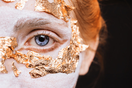 Blue eye closeup. A girl with an unusual make-up with gold leaf. Anonym. Masquerade Halloween