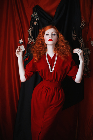 A woman with red hair in a red fitting dress. Red-haired girl with pale skin and blue eyes with a bright unusual appearance with beads around her neck. Noir woman Stock Photo