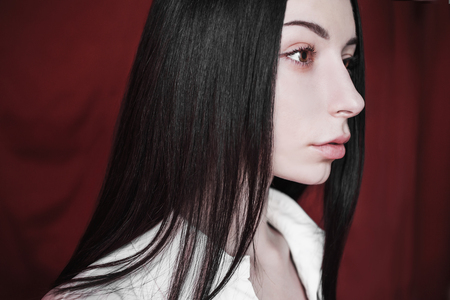 Emotional portrait of brunette girl with long straight black hair with a natural make-up on a red background. Woman in white unbuttoned shirt Stock Photo
