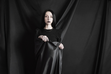 Emotional portrait of brunette girl with long straight black hair with a natural make-up on a black background. Woman in black dress wrapped in black cloth. Femme fatale witch