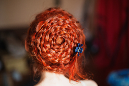 dutch girl: A woman with red curly hair braided in a braid in a white dress. Red-haired girl with pale skin. Pin-up girl makeup. Dutch braid closeup
