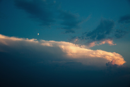 Blue sky with white and blue, and pink clouds. Clear sky. Moon in the sky