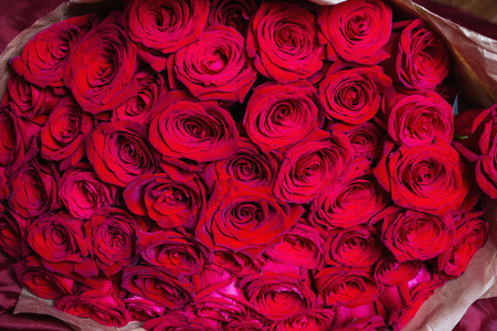Big beautiful bouquet of red roses. Texture colors. A gift for a wedding, birthday, Valentines Day.