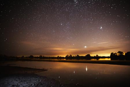 아름 다운 밤 별이 빛나는 풍경. 별 물에 반영. 천체 사진술. 별이 빛나는 하늘을 지 웁니다. 느린 셔터 속도. 장엄한 하늘.