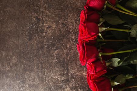 장미는 어두운 대리석 테이블 위에 놓여 있습니다. 빨간 장미 큰 아름 다운 꽃다발입니다. 텍스처 색상. 결혼식, 생일, 발렌타인 데이 선물. 텍스트 및  스톡 콘텐츠