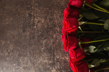Roses lie on a dark marble table. Big beautiful bouquet of red roses. Texture colors. A gift for a wedding, birthday, Valentines Day. Space for text and design. Flat lay, copyspace. Reklamní fotografie