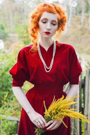 빨간 머리를 가진 여자와 손에 노란색 꽃의 꽃다발 빨간 드레스. 창백한 피부, 파란 눈 및 그녀의 목에 구슬 목걸이와 함께 밝은 비정상적인 모습을 가 스톡 콘텐츠
