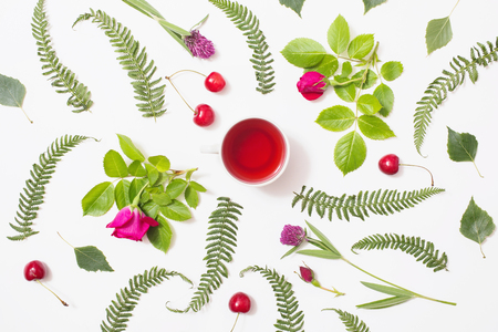 Red tea in a cup, green blades of grass with purple flowers