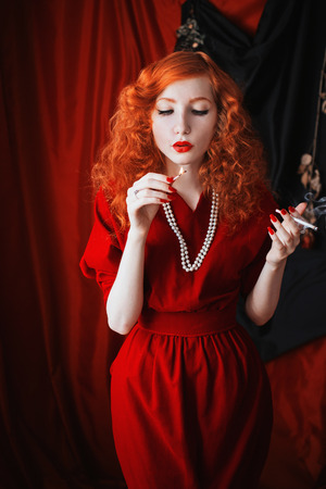 빨간 입술에 빨간 머리를 가진 여자는 그녀의 입에 담배와 드레스. 창백한 피부와 파란 눈을 가진 red-haired 소녀, 그녀의 목에 구슬과 밝은 비정상적인