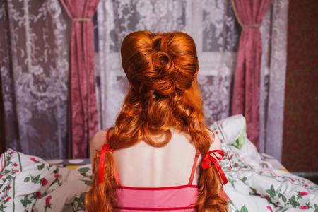 긴 빨간 곱슬 머리를 가진 여자는 머리 띠와 담요 아래 침대에서 잠옷으로 모였다. red-haired 여자는 침대에 침실에서 카메라에 다시 앉아있다. Updo