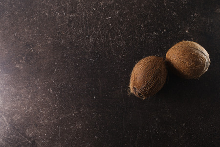 Coconut on a dark marble background. Exotic large walnut