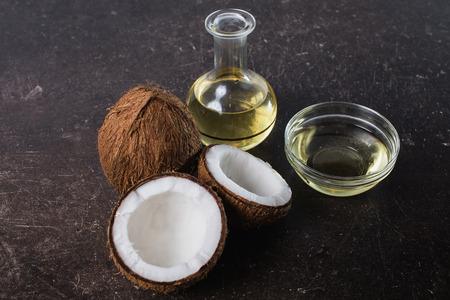 코코넛 및 코코넛 오일 어두운 대리석 백그라운드입니다. 이국적인 큰 호두. 개인 관리. 스파 트리트먼트