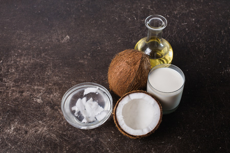 Coconut and coconut milk and oil on a dark marble background. Exotic large walnut. Personal care. Spa treatments 스톡 콘텐츠