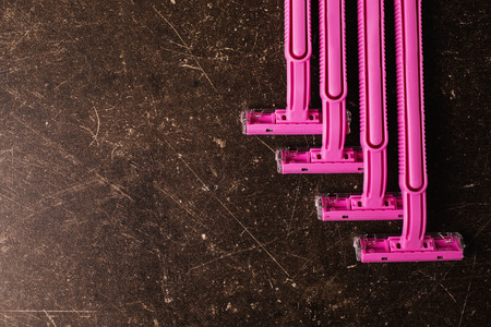 어두운 대리석 배경에 분홍색 면도기. 위생 제품