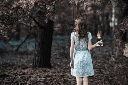 등유 램프와 아주 귀여운 어린 소녀입니다. 인형 모양. 자연에 청록색 드레스에 갈색 머리를 가진 여자. 긴 머리. 자연광. 모델 자연에 포즈입니다. 손