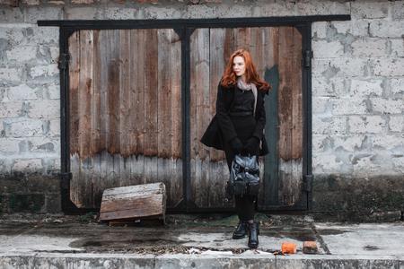 검은 옷에 긴 빨간 머리를 가진 눈에 띄는 소녀. 검은 코트와 오래 된 벽의 배경에 포즈 손에 배낭에있는 여자. 여성 거리 패션 스타일입니다. 아름다운