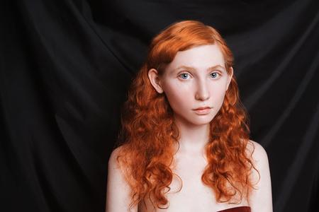 검정색 배경에 긴 곱슬 빨간 흐르는 머리를 가진 여자. 창백한 피부, 파란 눈, 메이크업없이 밝은 비정상적인 모습을 가진 나가서는 소녀. 자연미. 르네