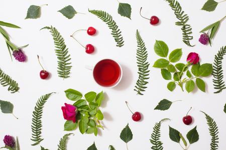 보라색 꽃, 잎, 자작 나무 나뭇 가지와 잔디의 컵, 녹색 잎 붉은 꽃, 녹색 고 사리와 로즈, 흰색 배경에 잘 익은 체리 거짓말. 평면 누워, 상위 뷰입니다.