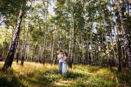 어두운 머리와 녹색 배경에 awhite 셔츠에 남자를 포옹하는 여름 드레스에 머리에 화 환을 가진 갈색 눈을 가진 아름 다운 소녀. 화창한 날 숲에서 몇 사