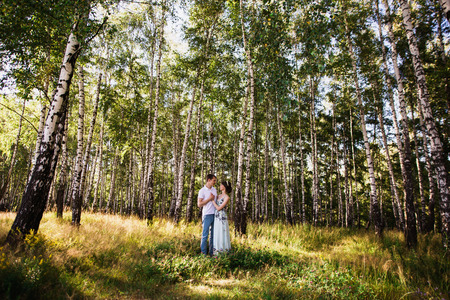 Beautiful girl with dark hair and brown eyes with a wreath on head in summer dress hugging a man in awhite shirt on a green background. Loving couple in the forest on a sunny day. To love each other Reklamní fotografie
