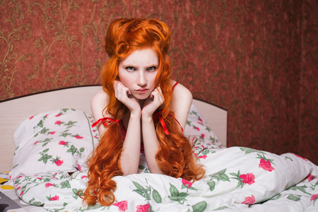 Woman with long red curly hair gathered into braids in nightgown in bed under a blanket. Red-haired girl with a pretty face, pale skin, blue eyes and bright unusual appearance in the bedroom
