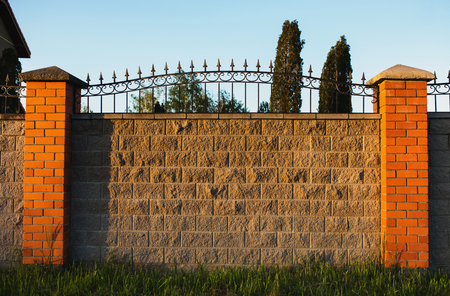 High fence made of gray stone with red brick shutters and forged metal fence