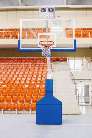 Ring and shield for playing basketball. Orange chairs stand in a row in a covered stadium. Tribune for fans 스톡 콘텐츠