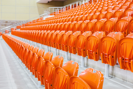 Orange chairs stand in a row in a covered stadium. Tribune for fans